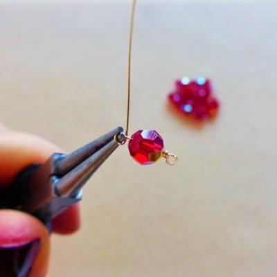 Enfilez une perle ronde sur le fil et faites la même boucle de l\u0027autre côté.